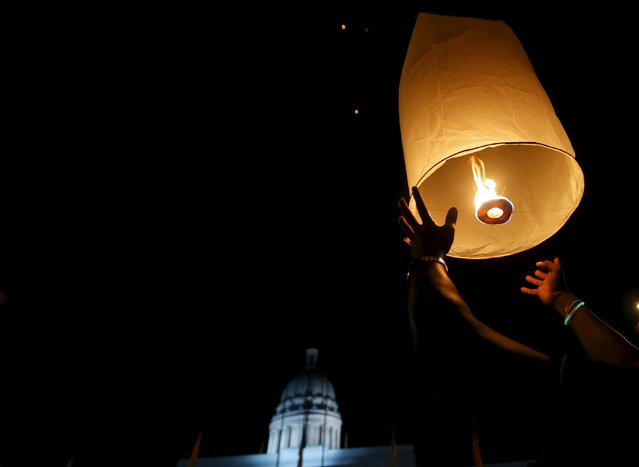 A man releases a floating lantern to mark Earth Hour in Colombo, Sri Lanka March 19, 2016. (Photo by Dinuka Liyanawatte/Reuters)