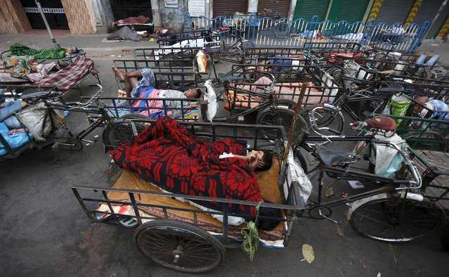 Cycle rickshaw drivers sleep in their rickshaws along a roadside early morning in Kolkata, India, March 10, 2016. (Photo by Rupak De Chowdhuri/Reuters)