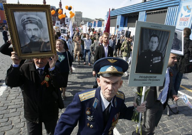People hold pictures of World War Two soldiers as they take part in the Immortal Regiment march during the Victory Day celebrations at Red Square in Moscow, Russia, May 9, 2015. (Photo by Sergei Karpukhin/Reuters)