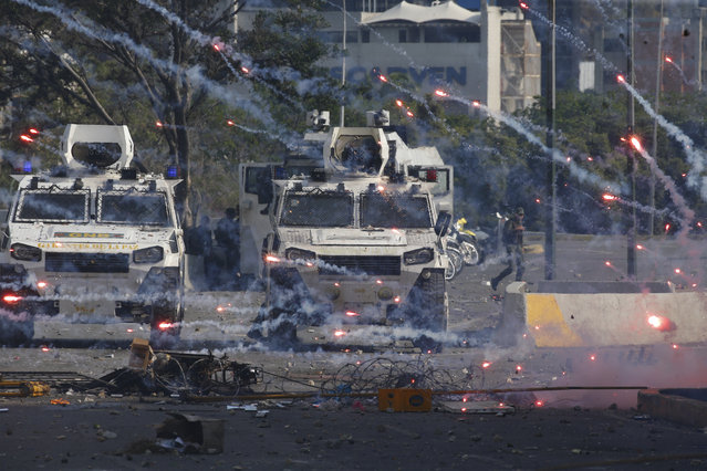 Fireworks launched by opponents of Venezuela's President Nicolas Maduro land near Bolivarian National Guard armored vehicles loyal to Maduro, during an attempted military uprising in Caracas, Venezuela, Tuesday, April 30, 2019. (Photo by Ariana Cubillos/AP Photo)