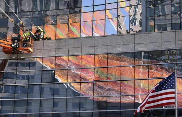 Workers, top left, secure lines that support a 600-foot sculpture, a portion of which is reflected in glass on a building, as it is suspended between high-rise buildings, Sunday, May 3, 2015, in Boston. The sculpture, that is to remain in place through October 2015, is made from over 100 miles of twine and utilizes over half a million knots in its construction. (Photo by Steven Senne/AP Photo)