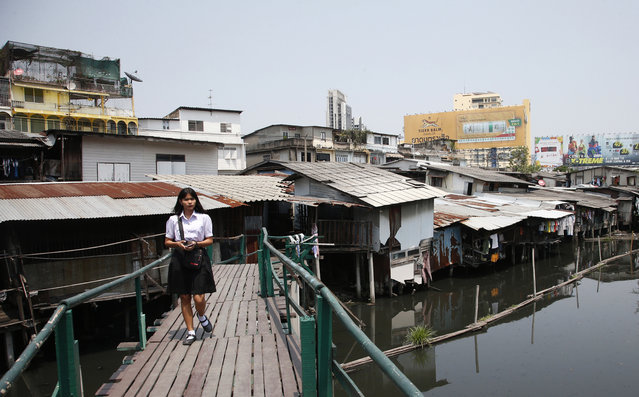 In this March 19, 2019, photo, Thai student walks over a footbridge bridge through dilapidated homes along the Phra Khanong canal in Bangkok, Thailand. Ahead of next weekend's general election, the widespread dissatisfaction among the country's poor with how the economy is doing may be balanced out by strong support for the junta from big business and wealthier Thais. For many voters, the still bigger issue is the role of the military after it took over in a 2014 coup. (Photo by Sakchai Lalit/AP Photo)