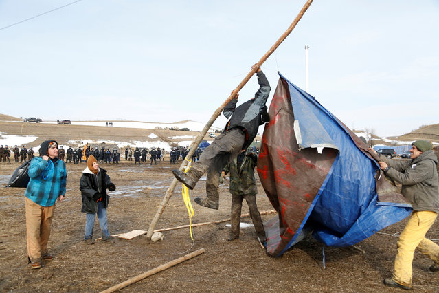 Protesters salvage a banner as law enforcement officers advance into the main opposition camp against the Dakota Access oil pipeline near Cannon Ball, North Dakota, U.S., February 23, 2017. (Photo by Terray Sylvester/Reuters)