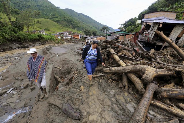 Residents cross in front of the ruins of a house, after a landslide close to the municipality of Salgar in Antioquia department, Colombia May 19, 2015. (Photo by Jose Miguel Gomez/Reuters)