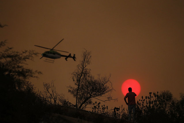 Video journalist Chris O'Neal records the sun visible through thick smoke from a wildfire as a helicopter flies past him Wednesday, August 8, 2018, in Lake Elsinore, Calif. (Photo by Jae C. Hong/AP Photo)