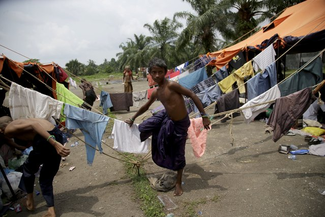 "In this May 22, 2015, photo, Hussein Ahmed, 12, walks between tents at a temporary shelter in Bayeun, Aceh Province, Indonesia. In an interview with the Associated Press Ahmed said, ""I was born in Myanmar, but they don't want me. I tried to go to Thailand or Malaysia, but I can't go anywhere because they don't want me"". (Photo by Tatan Syuflana/AP Photo)"
