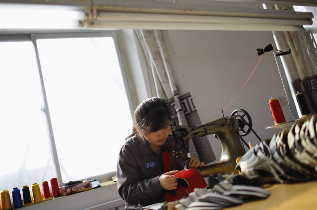 A North Korean worker sews inside a temporary soccer shoe factory at a rural village on the edge of Dandong October 24, 2012. (Photo by Aly Song/Reuters)