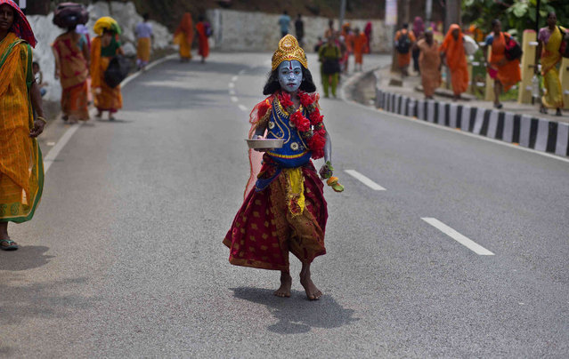 A boy dressed as Hindu goddess Kali asks for alms on a road near the Kamakhya Hindu temple ahead of the Ambubachi festival in Gauhati, India, Friday, June 21, 2019. (Photo by Anupam Nath/AP Photo)