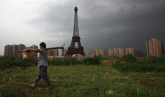 A farmer carrying a rake walks down a dirt road past a replica of the Eiffel Tower at the Tianducheng development in Hangzhou, Zhejiang Province August 1, 2013. Tianducheng, developed by Zhejiang Guangsha Co. Ltd., started construction in 2007 and was known as a knockoff of Paris with a scaled replica of the Eiffel Tower standing at 108 meters (354 ft) and Parisian houses. (Photo by Aly Song/Reuters)