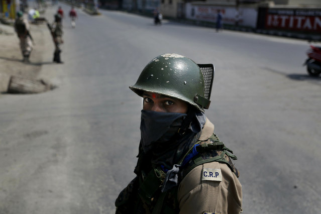 An Indian paramilitary soldier guards during restrictions in Srinagar, Indian controlled Kashmir, Monday, July 8, 2019. Authorities imposed restrictions in some parts of Srinagar after separatists called for a strike making the death anniversary of Kashmiri rebel leader Burhan Wani who was killed by Indian security forces on July 8, 2016. (Photo by Mukhtar Khan/AP Photo)