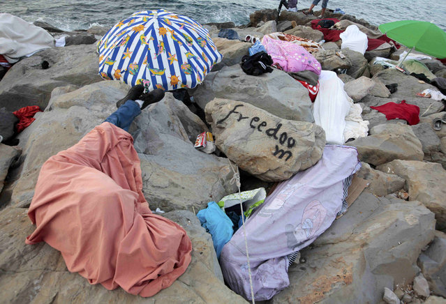 Migrants sleep covered by blankets on the rocks of the seawall at the Saint Ludovic border crossing on the Mediterranean Sea between Vintimille, Italy and Menton, France, June 17, 2015. Police on Tuesday began hauling away mostly African migrants from makeshift camps on the Italy-France border as European Union ministers met in Luxembourg to hash out plans to deal with the immigration crisis.  REUTERS/Eric Gaillard