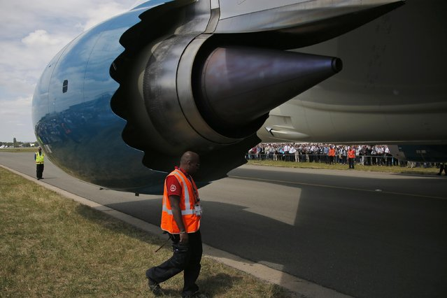 A safety employee walks by the left engine of the Boeing 787 Dreamliner prior to its demonstration flight at the Paris Air Show, in Le Bourget airport, north of Paris, Tuesday, June 16, 2015. Some 300,000 aviation professionals and spectators are expected at this weekends Paris Air Show, coming from around the world to make business deals and see aeronautic displays. (AP Photo/Francois Mori)