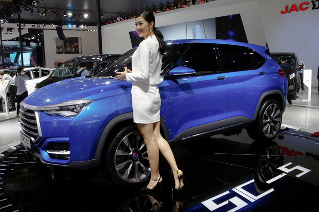 A girl poses by JAC SC5 concept car at the booth of Anhui Jianghuai Automobile Co. Ltd (JAC Motors) during the Auto China 2016 auto show in Beijing, China, April 26, 2016. (Photo by Kim Kyung-Hoon/Reuters)