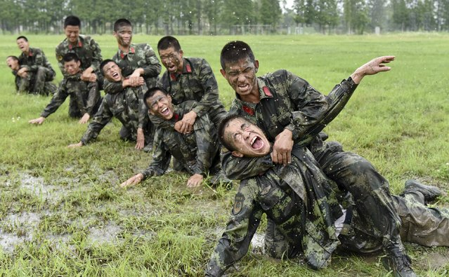 Paramilitary policemen react as they take part in a combat skills training session at a military base in Chaohu, Anhui province, China, June 25, 2015. (Photo by Reuters/China Daily)