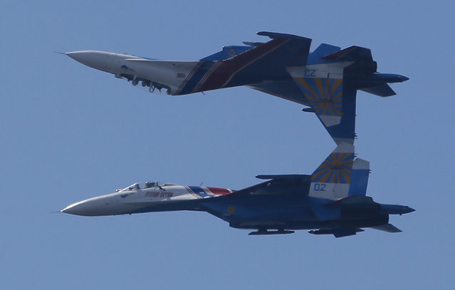 Su-27 jets of aerobatics team Russkiye Vityasy, or Russian Knights perform during the International Maritime Defence show in St.Petersburg, Russia, Thursday, July 2, 2015. (Photo by Dmitry Lovetsky/AP Photo)