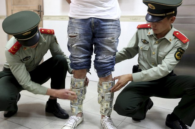 Paramilitary policemen take off U.S. dollars strapped around a man's legs, at the border of Hong Kong and Shenzhen, Guangdong province, April 24, 2014. According to local media, the man was found trying to smuggle in total of US$580,000 from mainland to Hong Kong. (Photo by Reuters/China Daily)