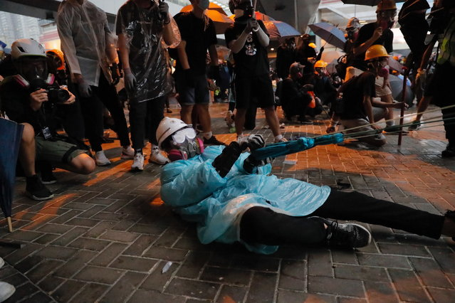 A protestor prepares to hurl an object at police officers in Hong Kong, Saturday, August 31, 2019. While other protesters marched back and forth elsewhere in the city, a large crowd wearing helmets and gas masks gathered outside the city government building. Some approached barriers that had been set up to keep protesters away and appeared to throw objects at the police on the other side. Others shone laser lights at the officers. (Photo by Kin Cheung/AP Photo)