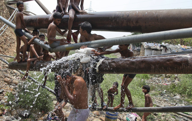 Indians cool themselves by bathing in water leaking from a pipe on the outskirts of Jammu, India, Saturday, May 7,2016. Much of India has been suffering from a heat wave for weeks along with a severe drought that has decimated crops, killed livestock and left at least 330 million Indians without enough water for their daily needs. (Photo by Channi Anand/AP Photo)