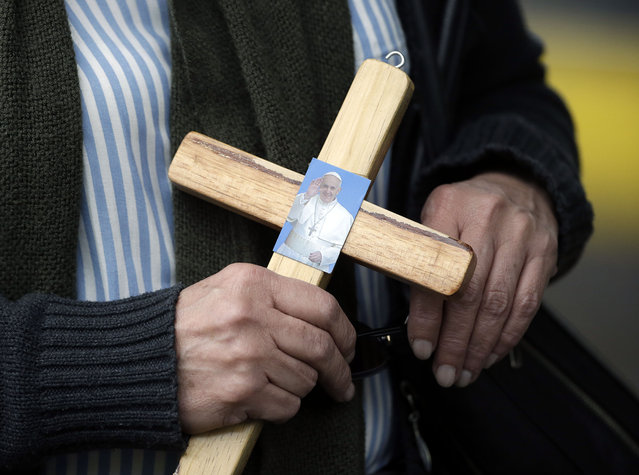A woman holds a cross decorated with Pope Francis' image as she waits for Pope Francis to arrive at Bicentennial Park where he will celebrate Mass in Quito, Ecuador, Tuesday, July 7, 2015. Pope Francis told faithful in Ecuador that being model Catholics is the best form of evangelization. (Photo by Gregorio Borgia/AP Photo)