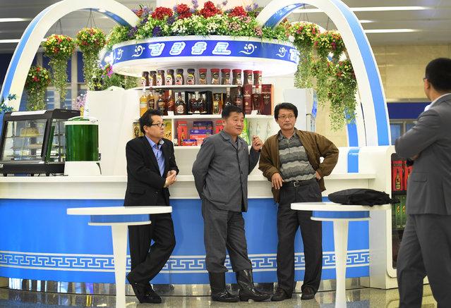North Korean men hang out at a liquor and coffee stand at the main airport  in Pyongyang, North Korea on May 3, 2016. (Photo by Linda Davidson/The Washington Post)