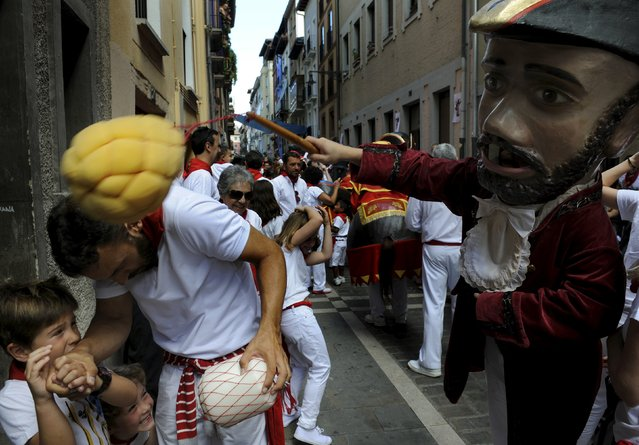 "A man is hit by a Kiliki during San Fermin festival's ""Comparsa de gigantes y cabezudos"" (Parade of the Giants and Big Heads) in Pamplona, northern Spain, July 8, 2015. ""Kilikis"", wearing oversized masks as they playfully hit bystanders with sponges on sticks, parade daily through the city accompanied by brass bands during the nine-day-long festival made popular by U.S. writer Ernest Hemingway. (Photo by Eloy Alonso/Reuters)"