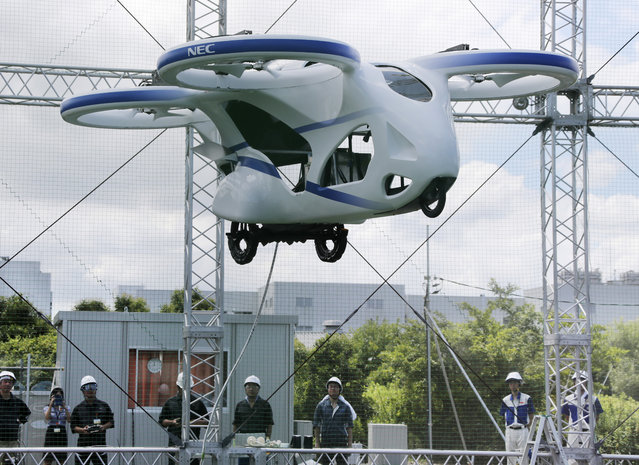 """NEC Corp.'s machine with propellers hovers at the company's facility in Abiko near Tokyo, Monday, August 5, 2019. The Japanese electronics maker showed a """"flying car"""", a large drone-like machine with four propellers that hovered steadily for about a minute. (Photo by Koji Sasahara/AP Photo)"""