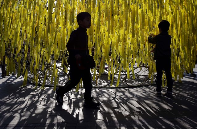 A boy ties a yellow ribbon of hope for the safe return of missing passengers and tribute to the victims of the sunken ferry Sewol, in Seoul, South Korea, on May 3, 2014. On April 16 the Sewol ferry carrying 476 passengers sunk off the island of Jindo. More than 302 passengers are dead or missing and the cause of the accident is still under investigation. (Photo by Chung Sung-Jun/Getty Images)