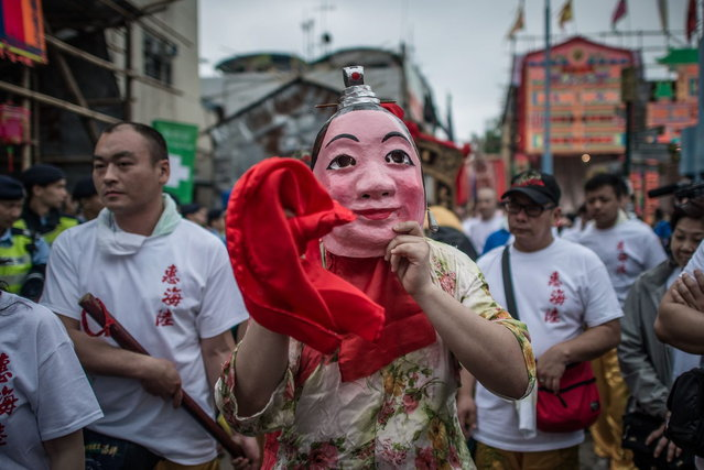 "A participant wears a mask during the ""Bun Festival"" on the island of Cheung Chau in Hong Kong on May 6, 2014. The traditional ""Bun Festival"" is held every year to placate the hungry ghosts of old pirates. Legend has it that buns bring good luck to the island's fisherman protecting them from the spirits of pirates that once lurked in the region. (Photo by Philippe Lopez/AFP Photo)"