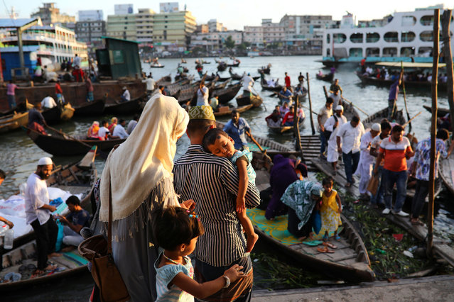People gather at a boat terminal to cross the Buriganga river by boat in Dhaka, Bangladesh, July 28, 2019. (Photo by Mohammad Ponir Hossain/Reuters)