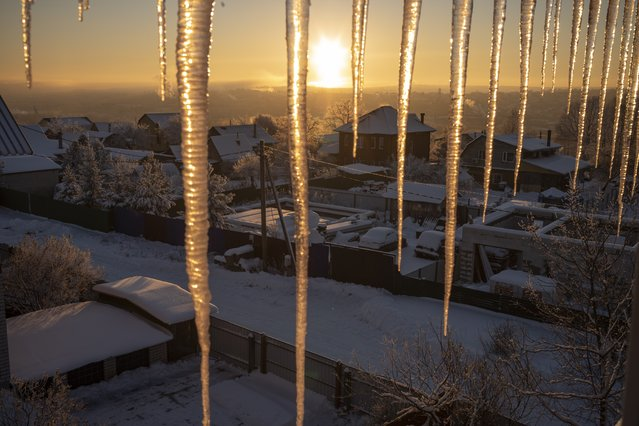 A frosty sunset is seen through icicles in Peremilovo village, 65 km (40,6 miles) north of Moscow, Russia, Sunday, December 16, 2018. Temperatures in the Moscow region on Sunday dropped to –12 degree Celsius (10 Fahrenheit). (Photo by Alexander Zemlianichenko/AP Photo)
