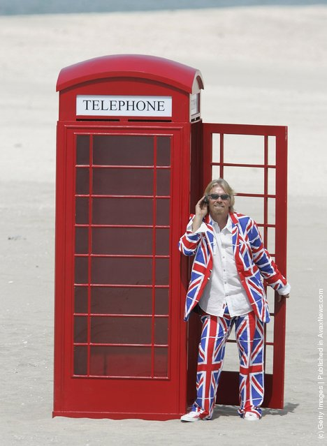 British Entrepreneur and businessman Sir Richard Branson poses next to a phone box during a photocall on a stretch of sand on the man-made island known as 'United Kingdom' in the new development, The World