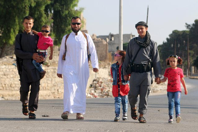 A man (C) walks with his family members, two of whom are fighters, on the first day of the Muslim holiday of Eid al-Fitr, which marks the end of the holy month of Ramadan, in a rebel-held area of Aleppo, Syria July 17, 2015. (Photo by Abdalrhman Ismail/Reuters)