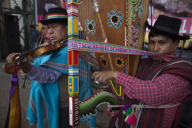 "Musicians play their instruments during a ""scissors"" dancer's performance in a national scissors dance competition at Lima's Exposition Park, May 18, 2014. The Danza de las tijeras, or scissors dance, is a traditional dance from the Peruvian southern region of the Andes, in which two or more performers take turns dancing while accompanied with music from a harp and a violin. Dancers would display various skills and moves, which include cutting the air with the use of a scissors. (Photo by Enrique Castro-Mendivil/Reuters)"