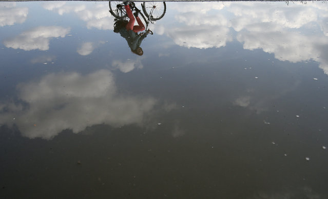 A cyclist is reflected in a puddle caused by a rainy period in Duisburg, Germany, Friday, May 16, 2014. Germany's weather forecast predicts the end of rain and warm and sunny weather for the upcoming week. (Photo by Frank Augstein/AP Photo)