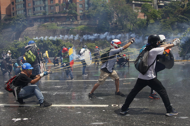 Anti-government protesters work together to aim a giant slingshot holding a glass bottle of fecal matter, at security forces blocking their march from reaching the Supreme Court in Caracas, Venezuela, Wednesday, May 10, 2017. (Photo by Ariana Cubillos/AP Photo)