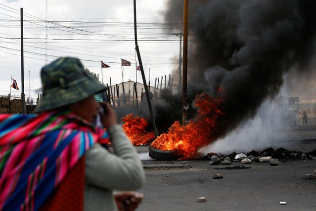 A person is seen near to a fire during a protest in Senkata, El Alto, Bolivia on November 19, 2019. Supporters of ousted Bolivian President Evo Morales ramp up protests and blockades of key transport routes, calling for caretaker President Jeanine Anez to step down and for Morales to return amid deadly clashes in the South American nation. (Photo by David Mercado/Reuters)