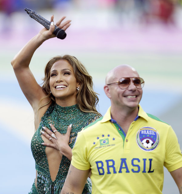 US singer Jennifer Lopez walks off the pitch after performing with rapper Pitbull before the group A World Cup soccer match between Brazil and Croatia, the opening game of the tournament, in the Itaquerao Stadium in Sao Paulo, Brazil, Thursday, June 12, 2014.  (Photo by Andre Penner/AP Photo)