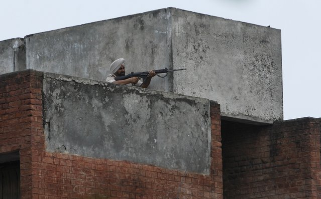 Indian policeman fires a shot during a gunfight in the town of Dinanagar, in the northern state of Punjab, India, Monday, July 27, 2015. (Photo by Channi Anand/AP Photo)