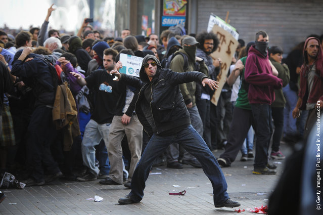 A demonstrator throws stones during heavy clashes with riot police during a 24-hour strike on March 29, 2012 in Barcelona, Spain