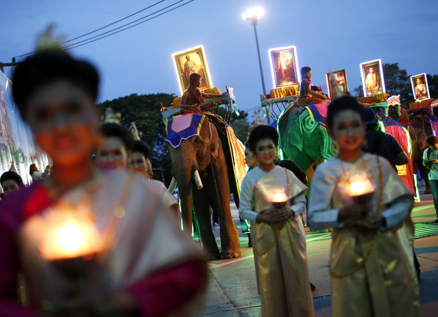 Thai women in traditional costumes hold candles and walk in front of elephants carrying pictures of Thai monarchs during a candlelit procession to mark the start of Buddhist Lent in Surin province, northeast of Thailand, July 29, 2015. The Buddhist Lent or Khao Pansa is a three-month long period beginning on the first day after the full moon of the eight lunar month which this year falls on July 31. (Photo by Rungroj Yongrit/EPA)