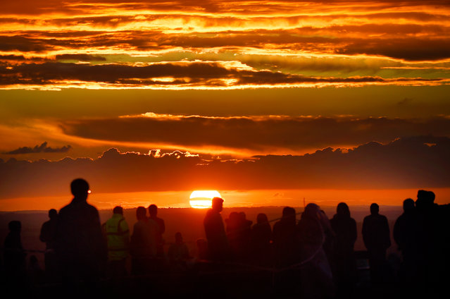 A group of Muslims wait for the sun to set to break their Ramadan fast on the top of Dunstable Downs with a firey sky as the back drop on June 03, 2017 in Dunstable, England. (Photo by Tony Margiocchi/Barcroft Images)