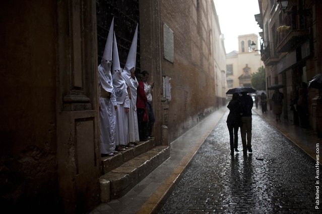 "Penitents from the ""La Candelaria"" brotherhood find shelter from the rain as a couple walks along the street during a storm in Seville, Spain, April 3., 2012 Most of the processions were canceled in Seville due to bad weather during the Easter Holy Week"