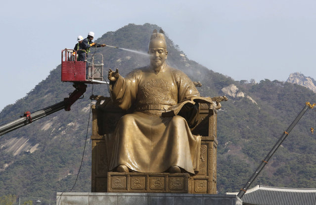 A worker sprays water onto the statue of King Sejong for a spring cleaning at the Gwanghwamun Plaza in Seoul, South Korea, Monday, April 10, 2017. King Sejong, the fourth king of the Joseon Dynasty (1392-1910), created the Korean alphabet, Hangul, in 1446. (Photo by Ahn Young-joon/AP Photo)