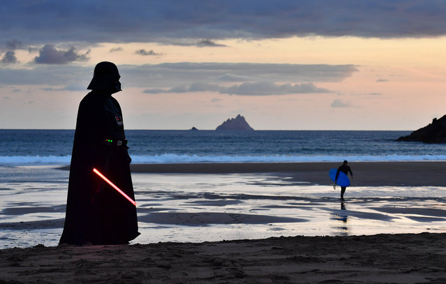 Garrison Ireland Leigon member John O'Dwyer dressed as the character Darth Vader looks out towards Skellig Michael island on May 4, 2019 in Portmagee, Ireland. The latest Star Wars movies such as The Last Jedi have featured the famous Skellig Michael islands situated off the coast of the small Irish fishing village. The May the Fourth Star Wars festival is taking place in the small County Kerry village for the second year running as millions of fans worldwide celebrate the science fiction series. The quiet costal setting has seen a sharp rise in the number of tourists and fans visiting the area. (Photo by Charles McQuillan/Getty Images)