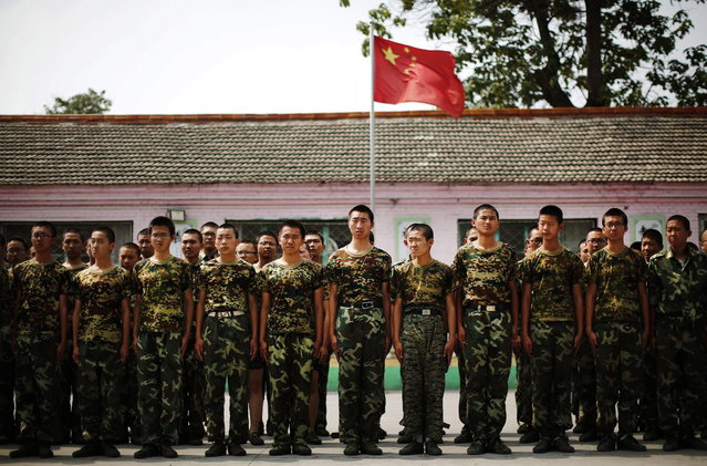 Students stand in front of the Chinese national flag as they prepare to take part in a military drill at the Qide Education Center in Beijing June 11, 2014. The Qide Education Center is a military-style boot camp which offers treatment for internet addiction. (Photo by Kim Kyung-Hoon/Reuters)