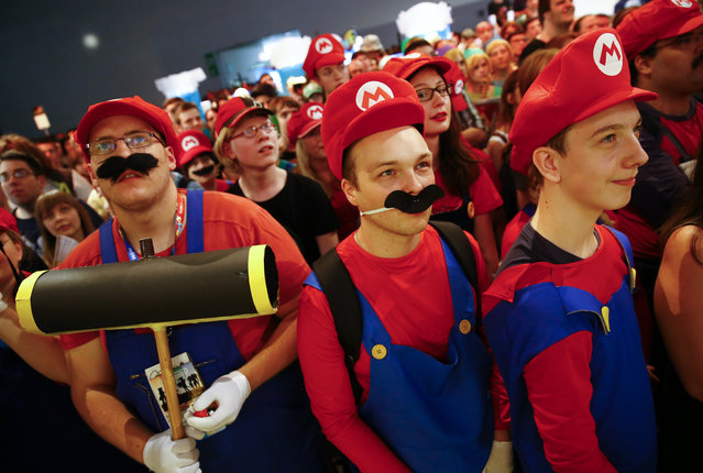 """Cosplayers dressed as character """"Mario"""" celebrate the 30th anniversary of """"Super Mario Bros."""" video games developed by Nintendo during the Gamescom 2015 fair in Cologne, Germany August 6, 2015. (Photo by Kai Pfaffenbach/Reuters)"""