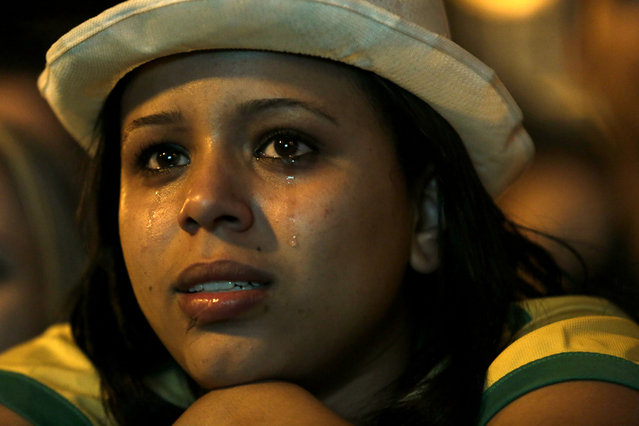 A Brazil soccer fan cries as she watches her team lose to Germany in a semifinal World Cup game on TV in Belo Horizonte, Brazil, Tuesday, July 8, 2014. (Photo by Bruno Magalhaes/AP Photo)