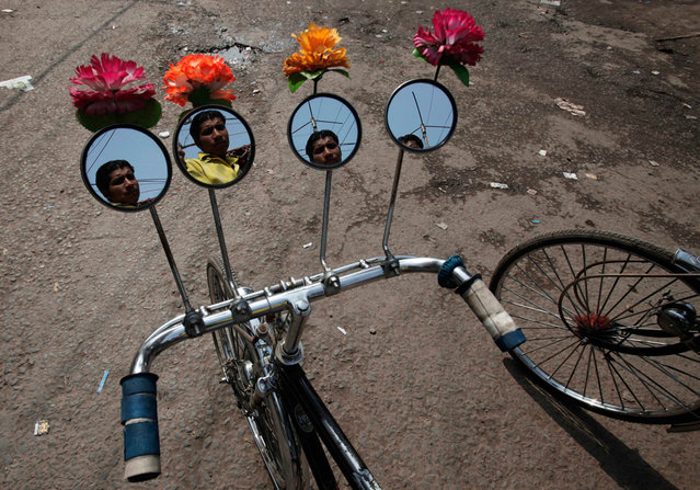 A rickshaw puller is reflected on the installed mirrors