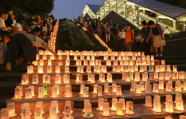 Visitors look at paper lanterns displayed for the Peace Candle Lights at Nagasaki Peace Park in Nagasaki, southwestern Japan, 08 August 2015, the eve of the 70th anniversary of the atomic bombing of the city on 09 August 2015. The atomic bombing of Nagasaki city killed about 74,000 people and injured about 75,000 people of 240,000 population in 1945. (Photo by Kimimasa Mayama/EPA)