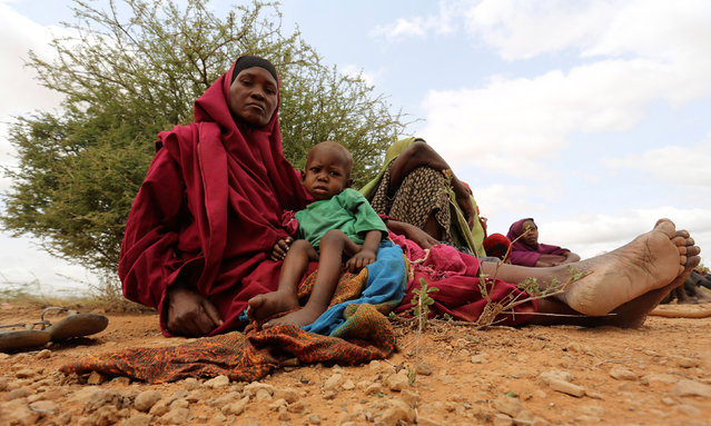 An internally displaced woman who fled flooding of the overflowed Shabelle river carries her child as they wait to receive relief assistance near Baledweyne town in central Somalia, June 22, 2016. (Photo by Feisal Omar/Reuters)
